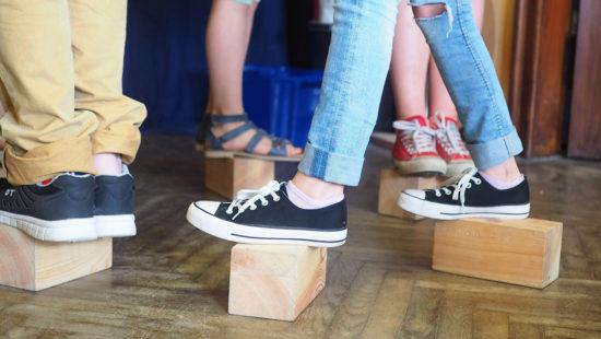 Schüler balancieren auf Holzklötzen.