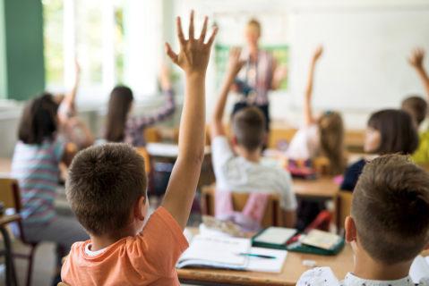 Mehrere Kinder in einem Klassenraum melden sich mit Handzeichen