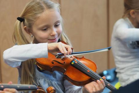 Eine Grundschülerin spielt ein Stück auf der Violine