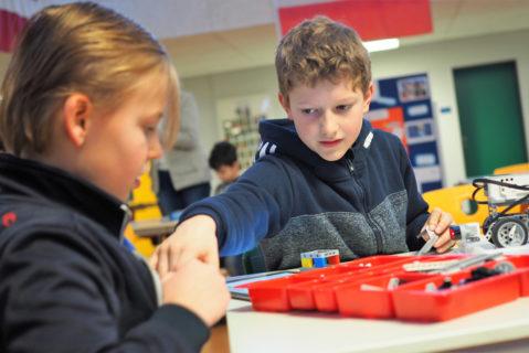 Zwei Grundschüler basteln mit einem Elektrobaukasten