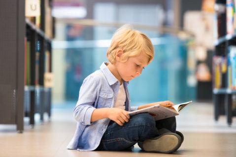 Ein kleiner Junge sitzt auf dem Boden einer Bibliothek und liest ein Buch