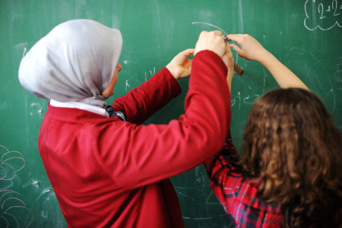 Zwei Schülerinnen – eine trägt ein Kopftuch – an der tafel
