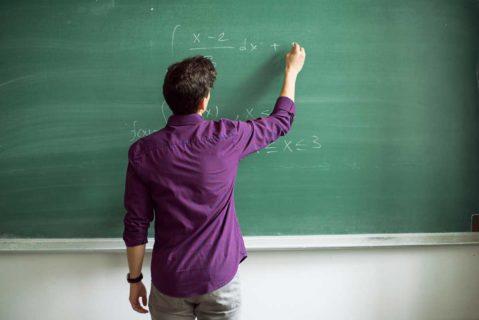 Ein Lehrer schreibt eine Mathematische Formel an die Tafel