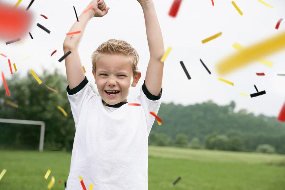 Ein kleiner Junge reißt die Arme hoch und Konfetti in Deutschlandfarben fällt herunter
