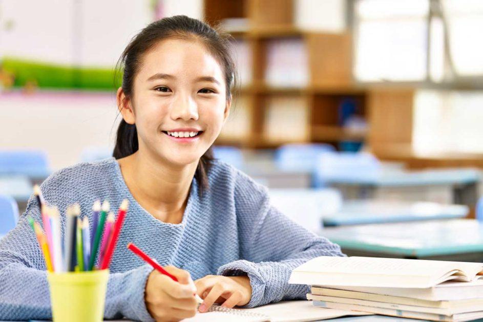 Eine junge Schülerin lächelt in die Kamera