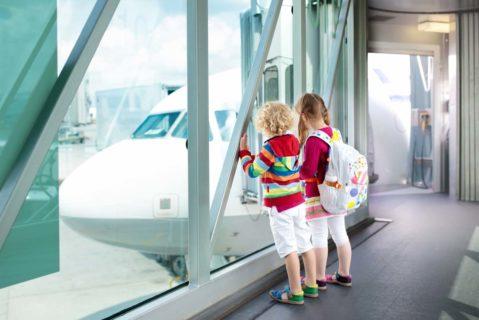 Zwei kleine Mädchen sehen sich am Flughafen ein Flugzeug an.