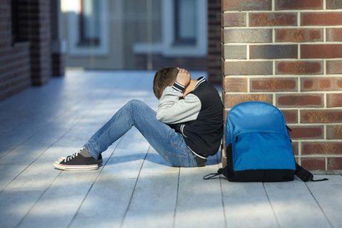 Ein Junge sitzt in einer Schule auf dem Boden