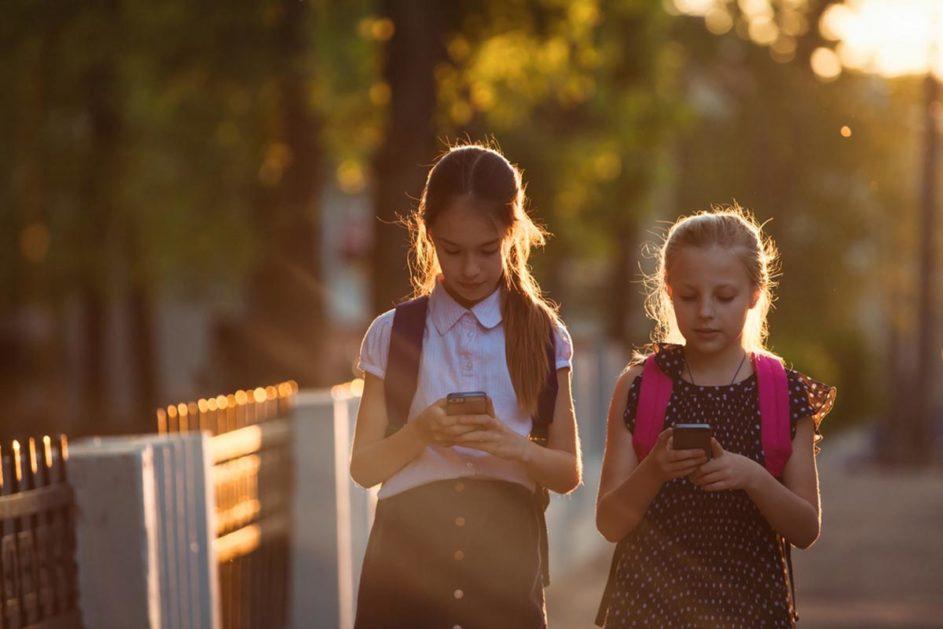 zwei Schülerinnen laufen und schauen aufs Handy