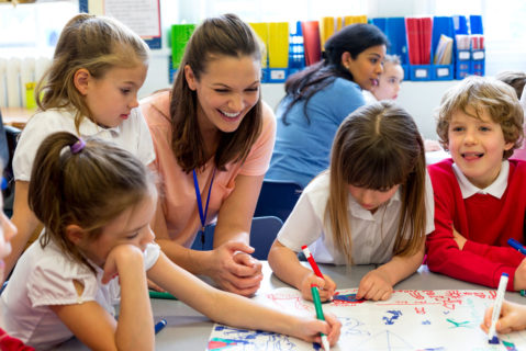Eine Grundschullehrerin im Unterricht mit ihren Schülerm