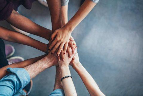 Viele Menschen legen ihre Hände aufeinander
