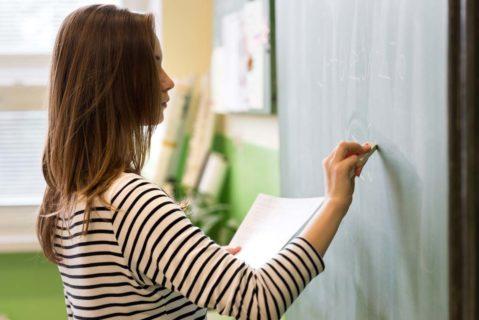 eine Lehrerin schreibt etwas an die Tafel