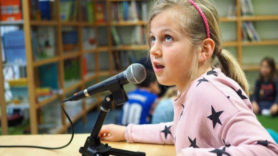 ein junges Mädchen spricht in ein Mikrofon