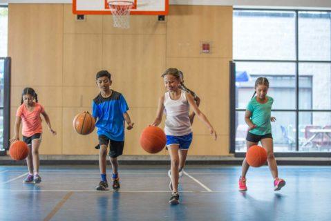 junge Schülen drippeln mit Basketball durch die Turnhalle