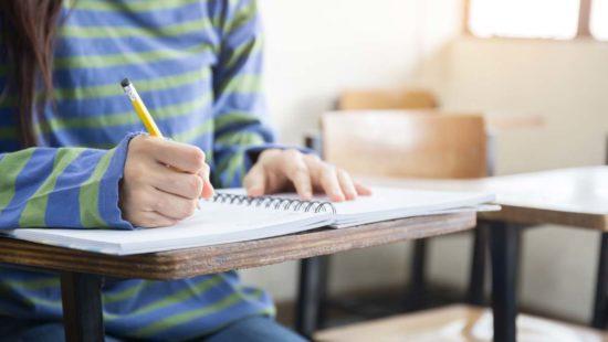 Ein Kind macht sich in der Schule Notizen
