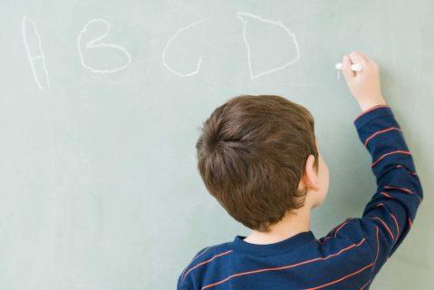 Ein Grundschüler Schreibt das Alphabet an die Tafel