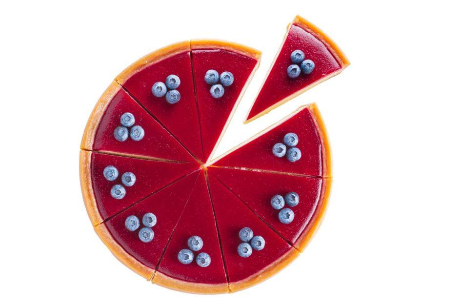 Ein Käsekuchen mit Fruchtopping in Stücke geschniten, ein Stück wird herausgenommen