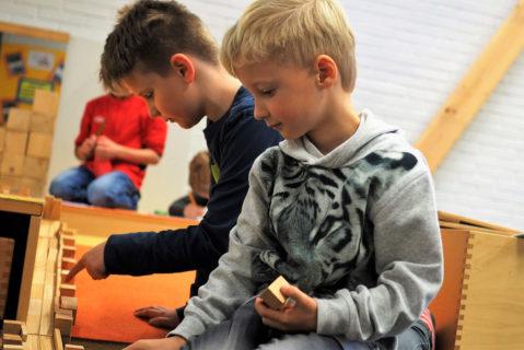 Zwei Jungen spielen mit Holzbauklötzen