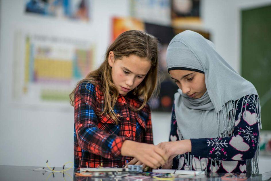 Zwei Schülerinnen arbeiten mit einem Elektrobaukasten