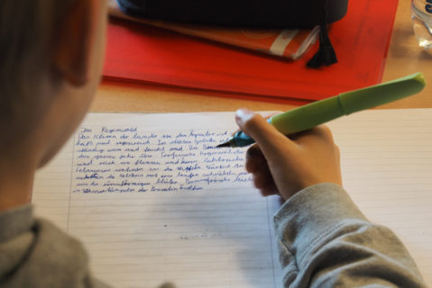 Ein Kind schreibt etwas in ein Heft.