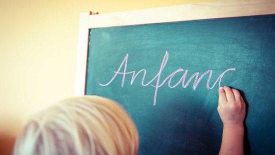 Kind schreibt Anfang auf eine Tafel
