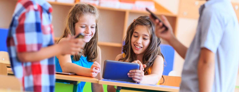 Schüler sitzen im Klassenzimmer und arbeiten mit Smartphones und Tablets