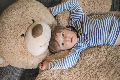 ein kleines Kind kuschelt mit einem sehr großen teddybär