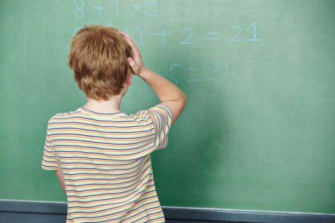 ein Schüler steht vor einer Tafel und überlegt