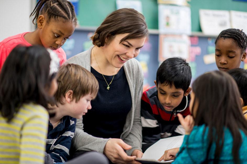 Eine junge Lehrerin liest ihren Schülern aus einem Buch vor