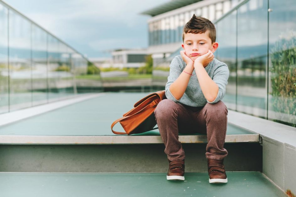 ein kleiner Junge sitzt gelangweilt auf einer Glasbrücke