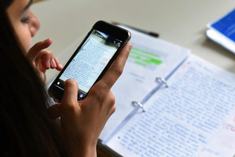 Eine Schülerin fotografiert Notizen