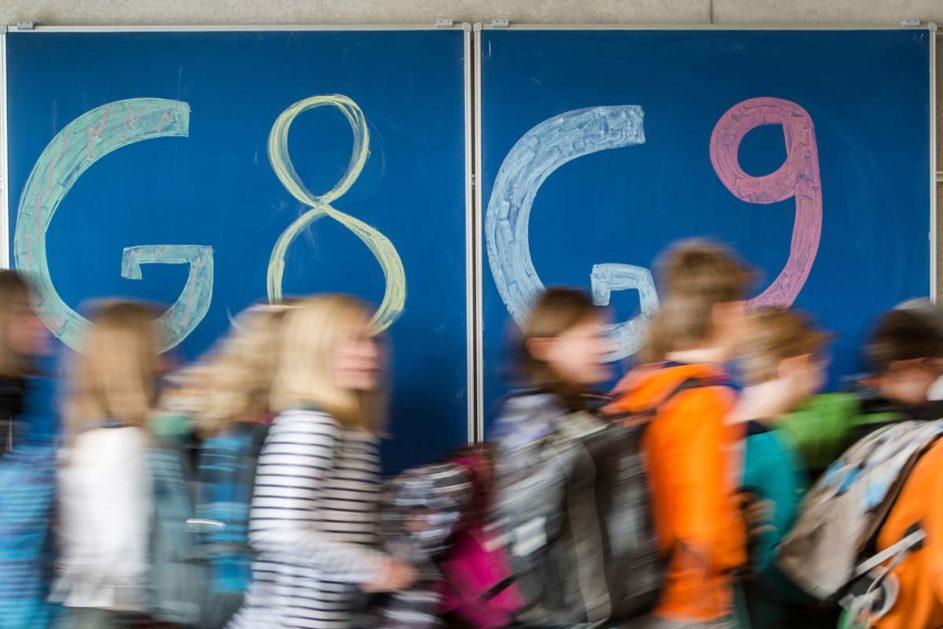 Schüler laufen an einer tafel vorbei, auf der Tafel steh G8 und G9