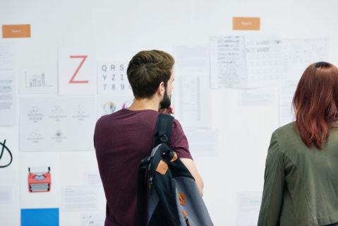 Ein Mann und eien Frau stehen vor einem Whiteboard