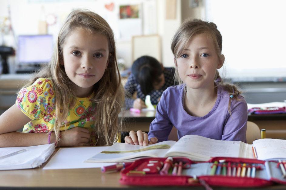 Zwei Schülerinnen sitzen im Klassenraum.