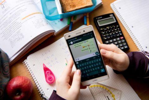 Eine Schülerin schreibt während der Hausaufgabenzeit Nachrichten.