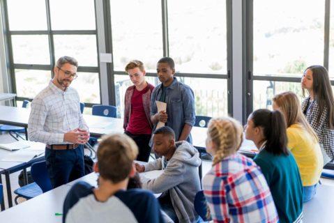 Ein Lehrer im Gruppengespräch mit seinen Schülern