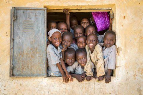 junge Kinder schauen aus einem Fenster.