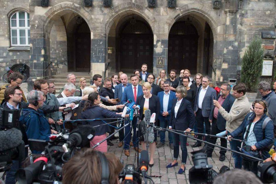 Bundesfamilienministerin vor dem Rathaus in Chemnitz umringt von Journalisten