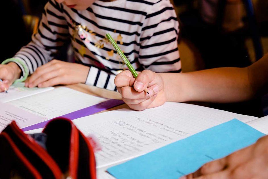 Zwei Kinder schreiben in ihre Hefte.