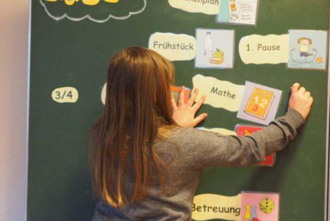 Eine Schülerin heftet einen Ablaufplan an die Tafel