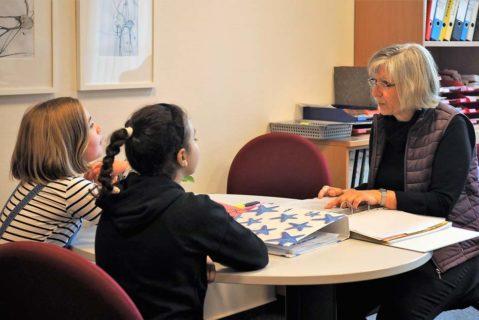 Schülerinnen und eine Lehrerin unterhalten sich.
