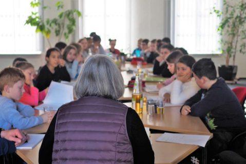 Schülerinnenund Schüler besprechen sich mit einer Lehrerin.