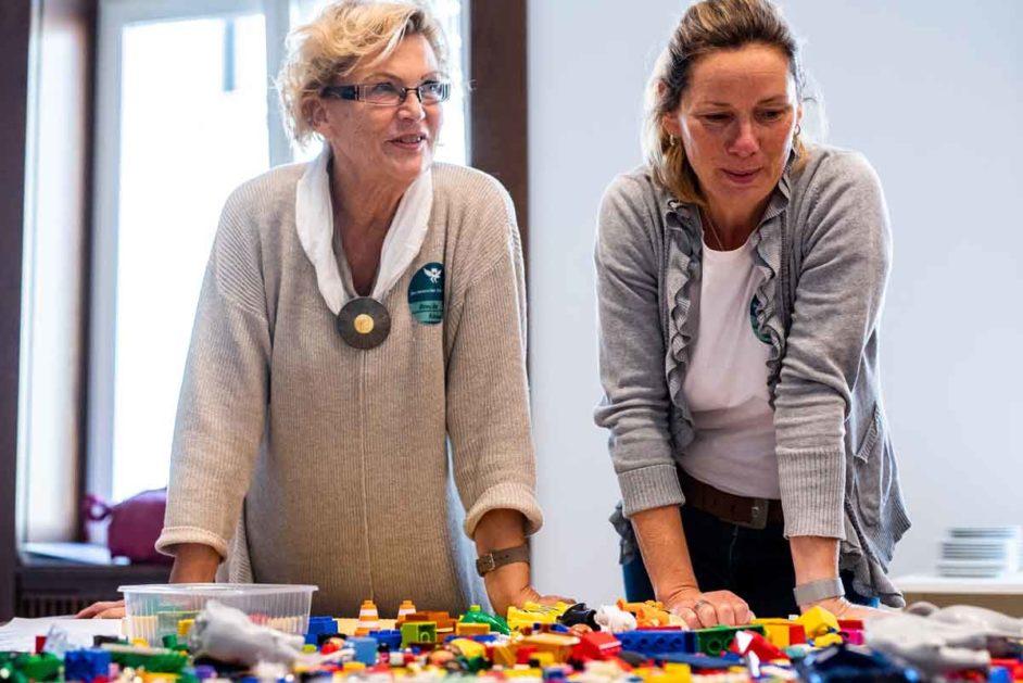 Monika Nebel und Claudia Hach vor einem Tisch mit Lego-Steinen
