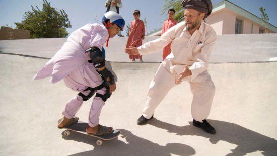 Titus Dittmann zeigt einem Jungen das Skateboarden