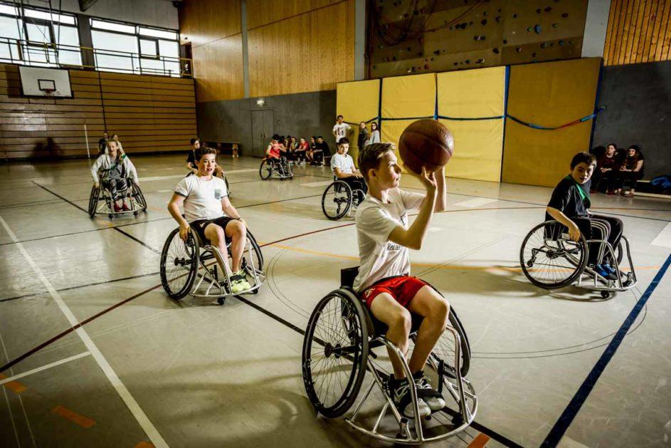 Rollstuhlfahrende Kinder spielen Basketball