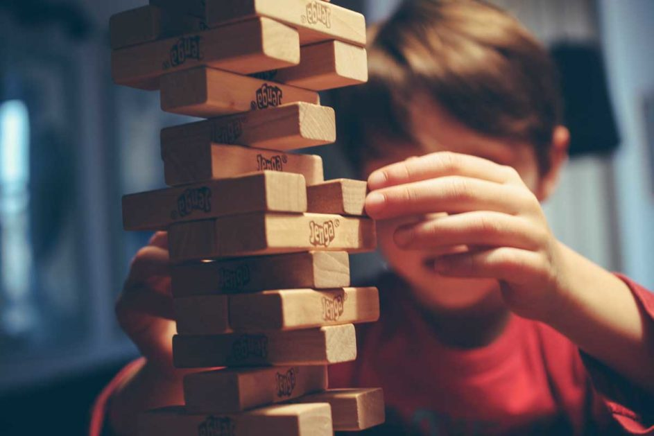 "Ein Junge baut einen ""Jenga""-Turm aus Holzklötzen"