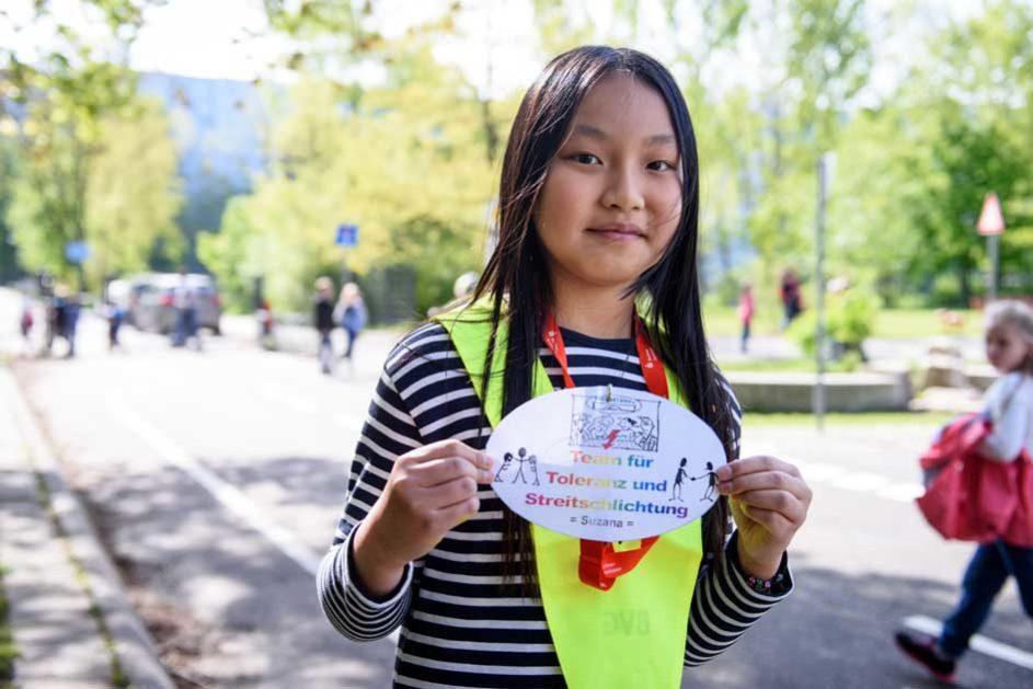 """Eine Streitschlichterin der Peter-Pan-Schule (School Turnaround) hält ein Zettel auf dem steht """"Team für Toleranz und Streitschlichtung"""""""