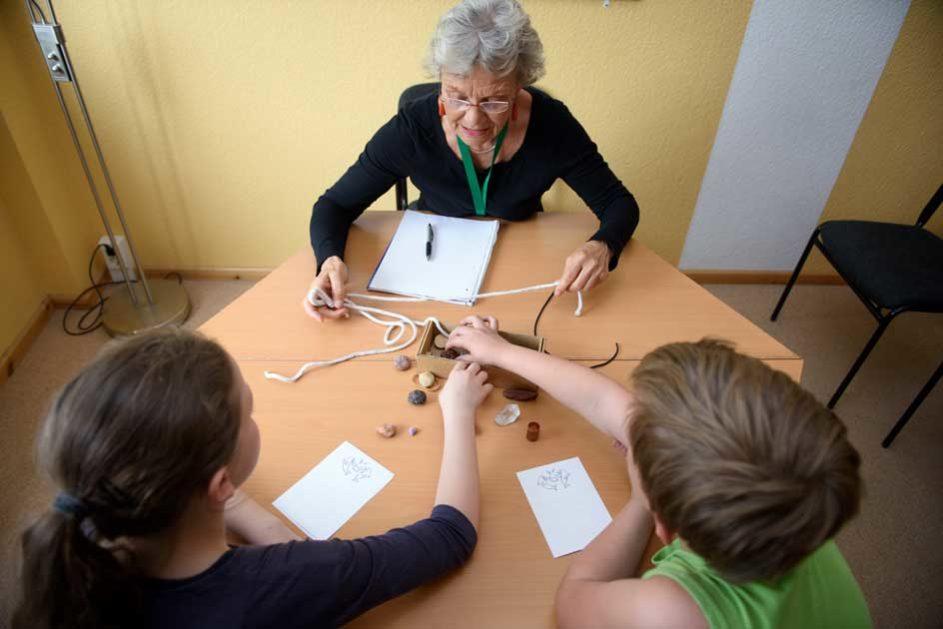 Lehrerin der Bücherwurm-Schule am Weiher (School Turnaround) im Gespräch mit Schülern, auf dem Tisch liegen Steine und Stricke