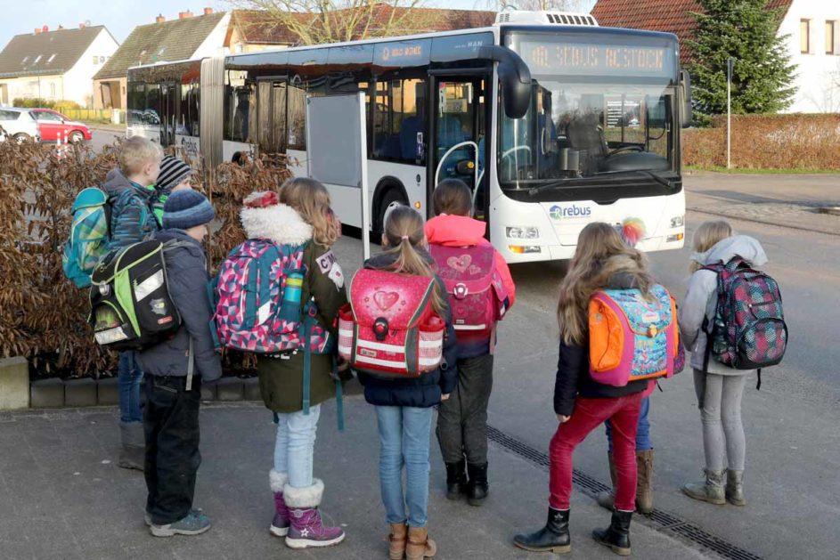 Grundschüler warten vor einem Schulbus