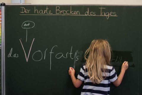 Schülerin steht bei einem Schreibtest an der Tafel (Symbolbild).
