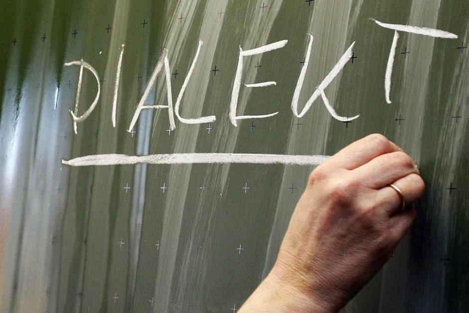 """Ein Lehrer schreibt """"Dialekt"""" an eine Tafel"""